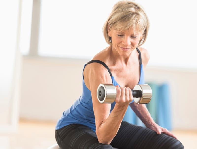 older woman using weights