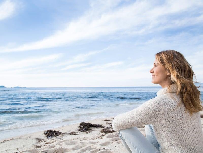 healthy older woman sitting on beach