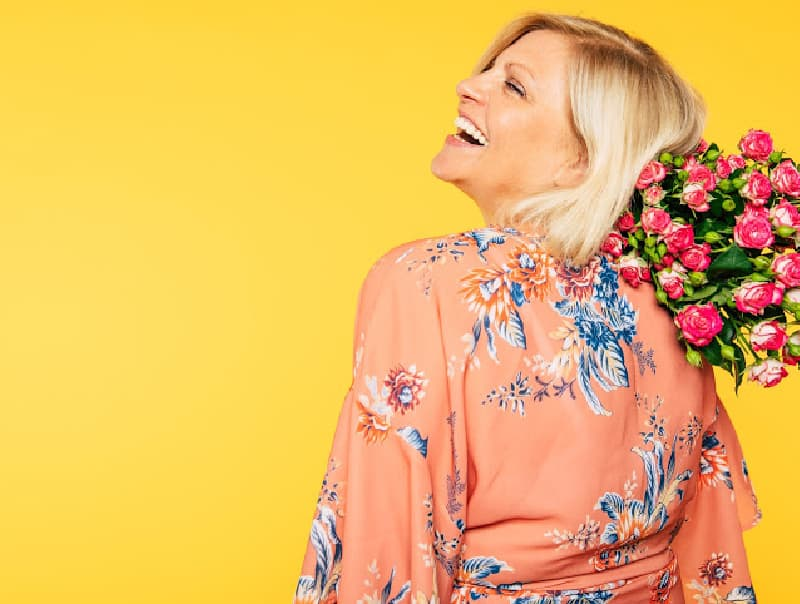 Woman holding flowers and laughing