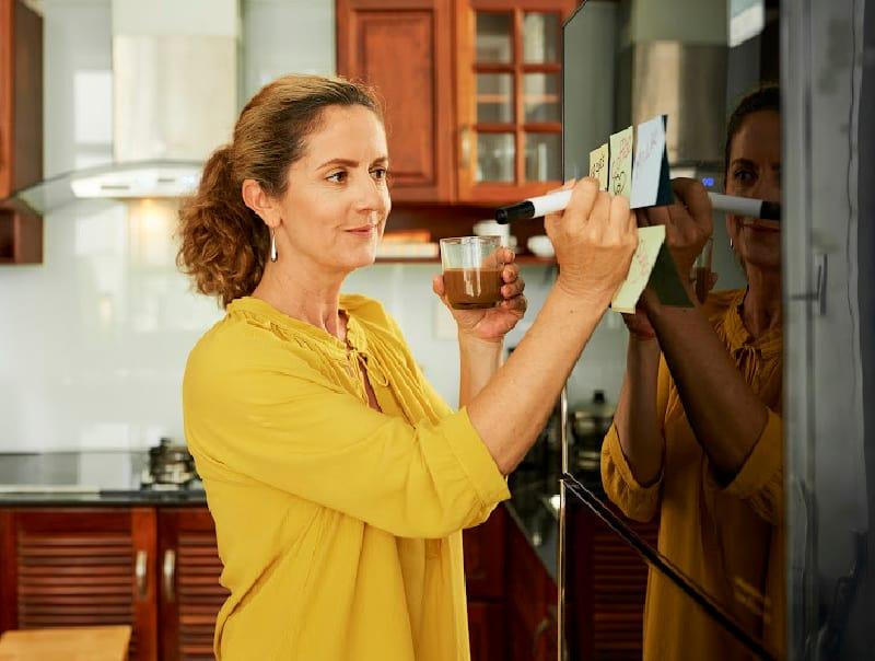 woman writing on post it notes on fridge