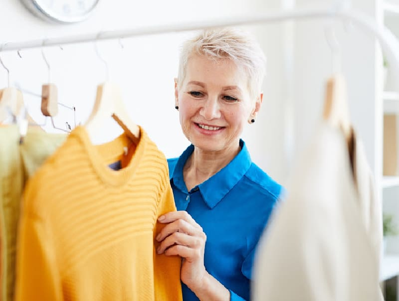 woman looking at yellow jersey on clothing rack in shop