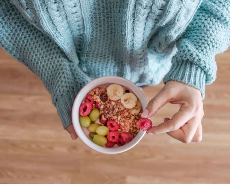 Woman holding granola and fruit in bowl