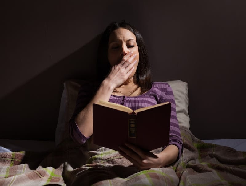 tired woman reading in bed