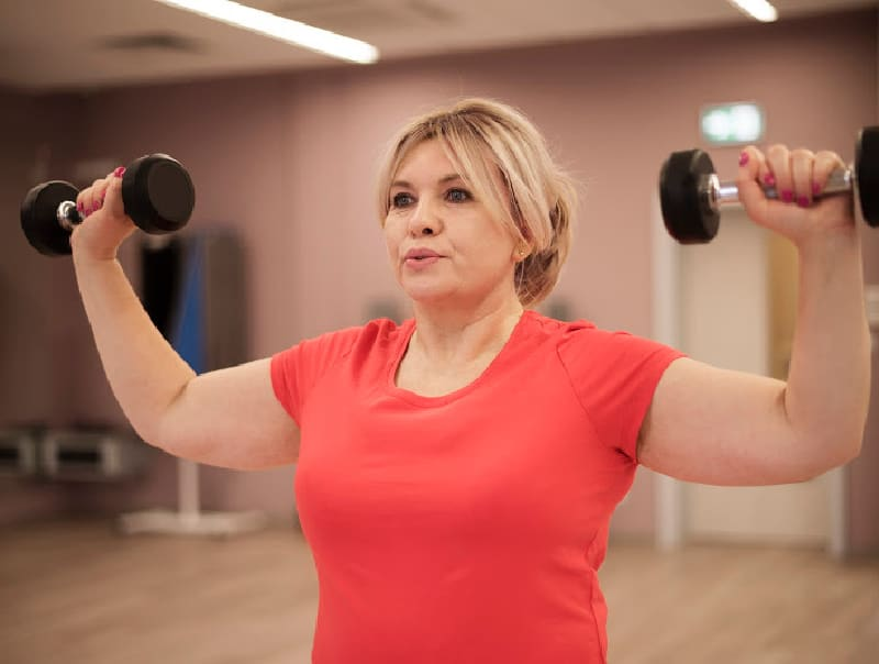 Women lifting weights to build muscle and speed up metabolsim