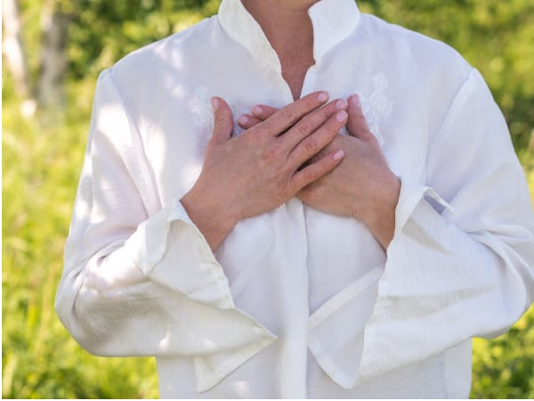 woman with hand on chest feeling breath