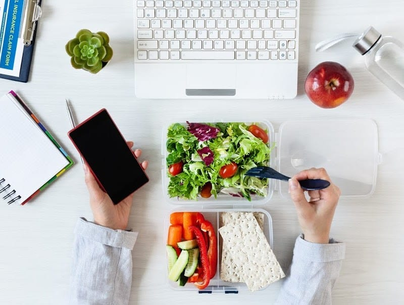 woman eating at desk with healthy food