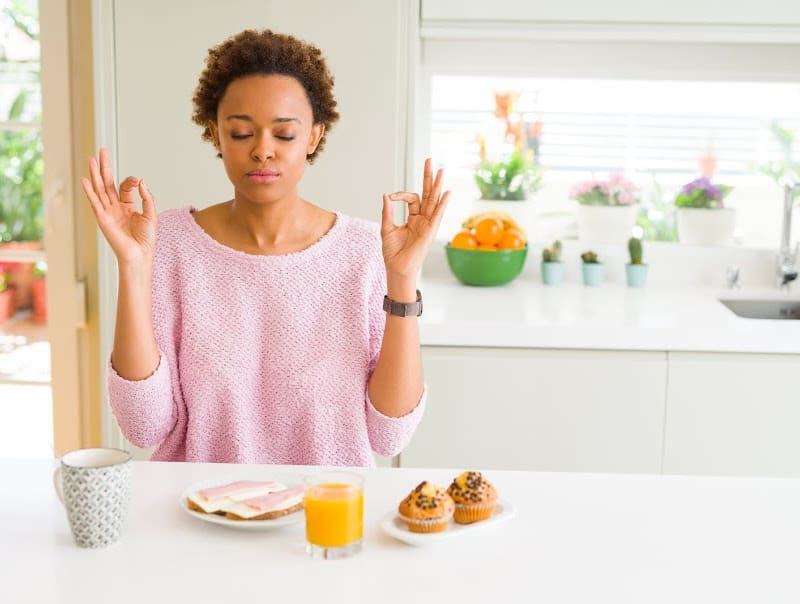 woman doing meditation while at kitchen table with food