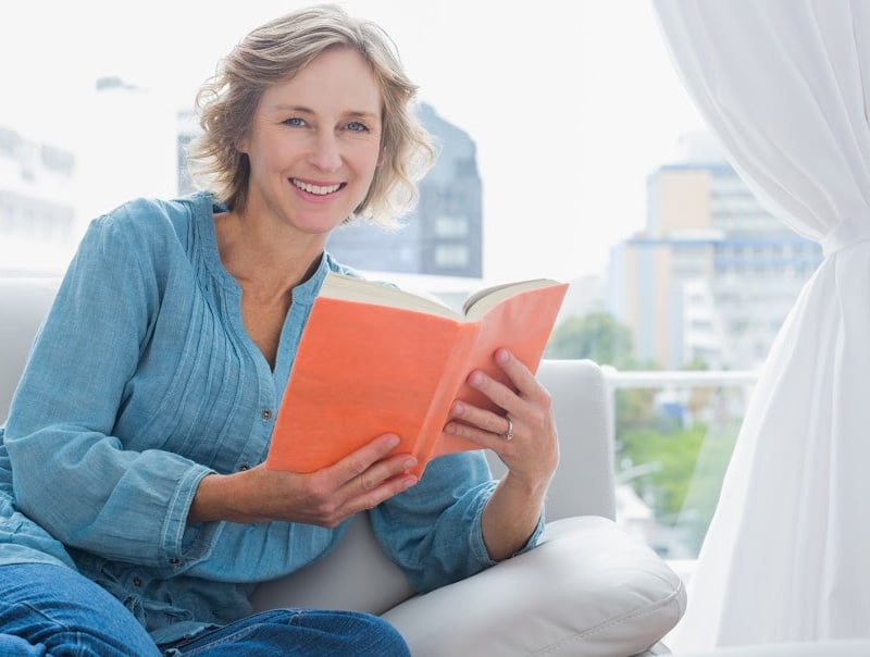 older woman on couch with book