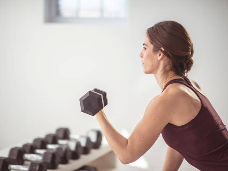 older woman lifting weights to help lose menopause belly fat