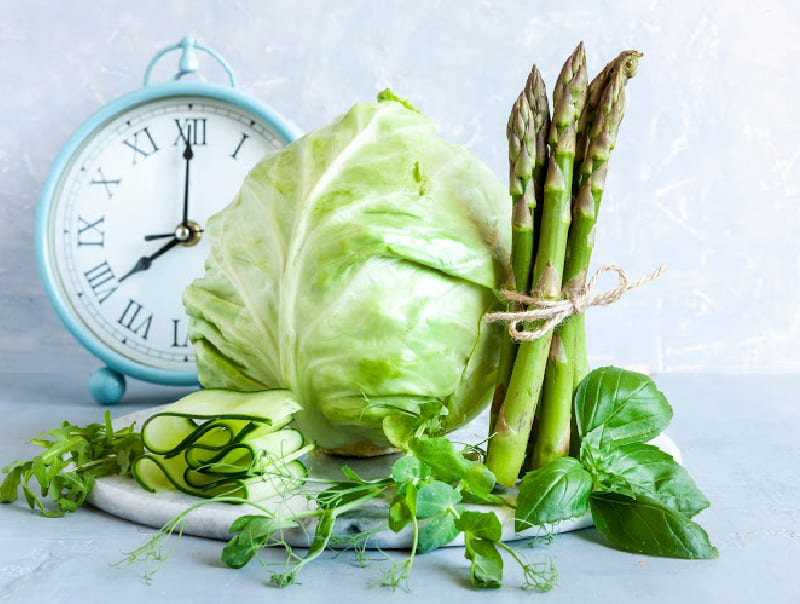 clock with healthy food indicating intermittent fasting