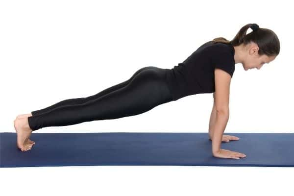Woman doing plank pose to lose belly fat in midlife