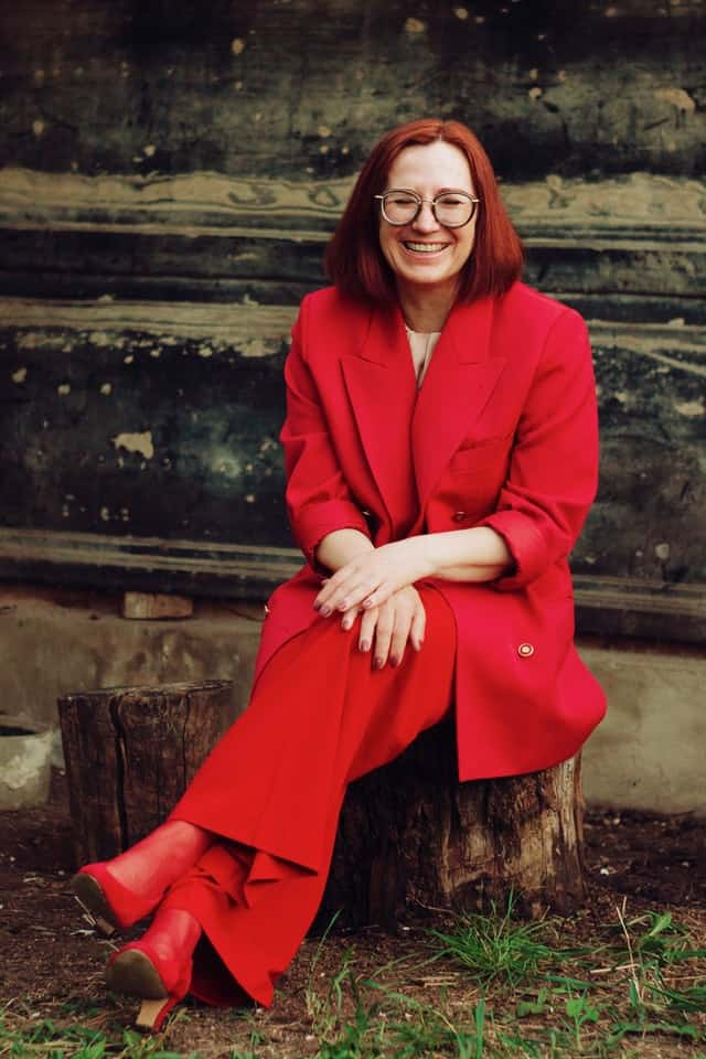 older woman with red suit on who has managed to balance her thyroid